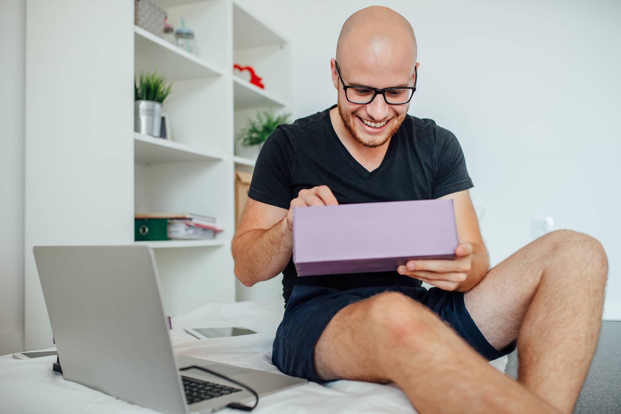man opening box in bedroom