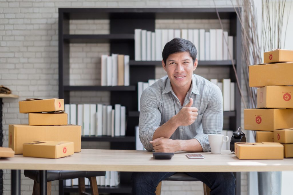 happiness business owner with box product and laptop on table successful business ideas concept