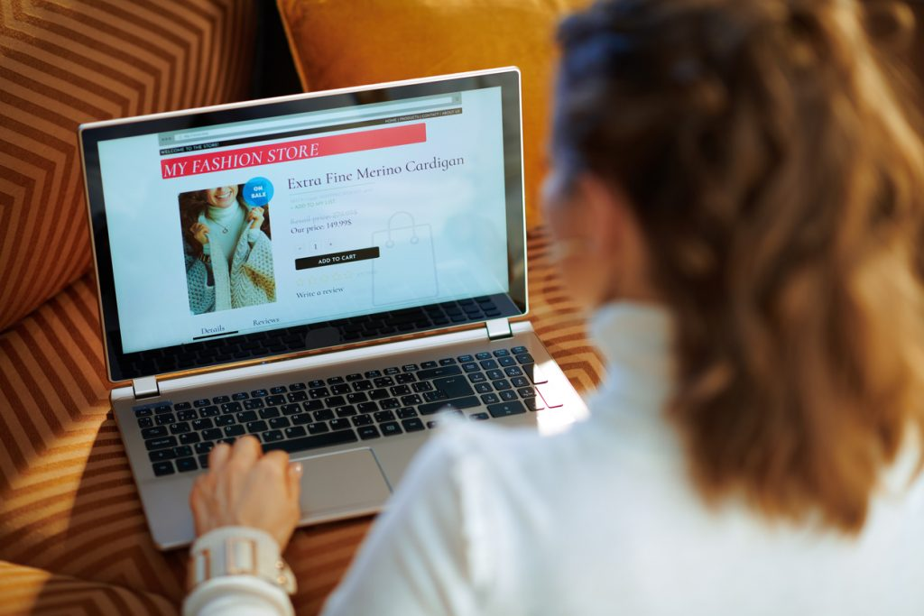 trendy woman ordering sweater in fashion online shop on laptop